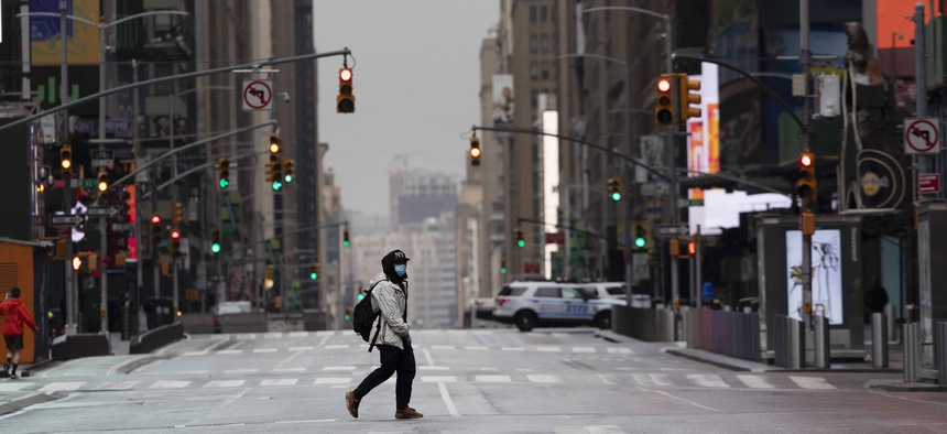 A man wearing a mask crosses the street in a quiet Times Square, Thursday, April 9, 2020, during the coronavirus epidemic.