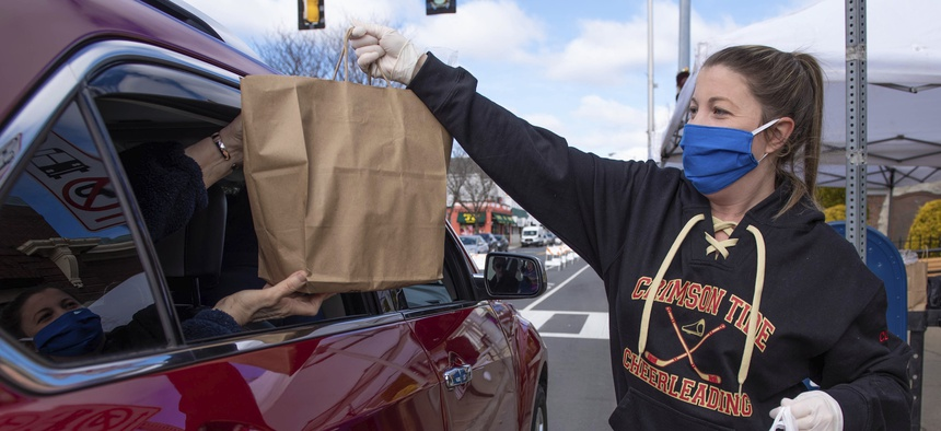 A food pantry worker in Massachusetts hands a bag of groceries to a person in a car.