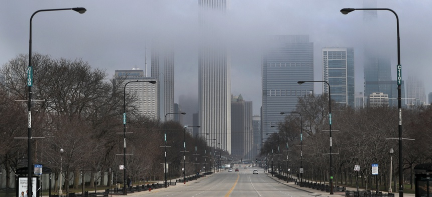 Fog lifts over Chicago and the usually busy Columbus Drive after people were ordered to stay at home. Illinois Gov. JB Pritzker's office estimates the budget shortfall for 2021 will top $6 billion because of the coronavirus-fueled economic downturn.