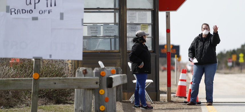 A New York State Department of Health worker instructs drivers to approach a kiosk at a COVID-19 drive-thru testing site at Jones Beach State Park on Long Island on March 18, 2020, in Wantagh, N.Y.