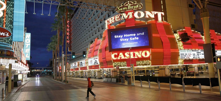 In this March 21, 2020, file photo, a man walks along a usually busy Fremont Street after casinos were ordered to shut down due to the coronavirus outbreak in Las Vegas.