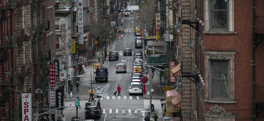 A woman pulls her grocery cart as she crosses the streets in Chinatown, on Thursday, March 19, 2020, in New York.