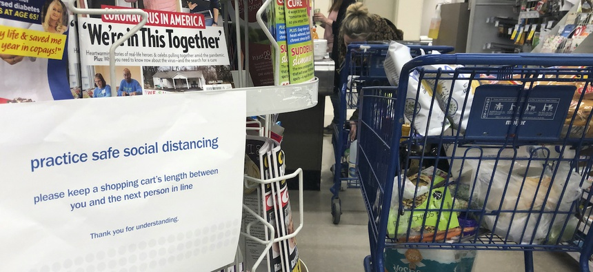 A sign alerts shoppers to practice social distancing, due to the coronavirus, while in the checkout line at a grocery store, Saturday, March 28, 2020 in Troy, Mich.