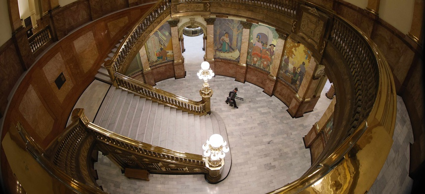 A lone television photographer passes through the rotunda of the State Capitol on the way to a news conference by Gov. Jared Polis to update the state's efforts to control the spread of the new coronavirus Friday, May 15, 2020, in Denver.