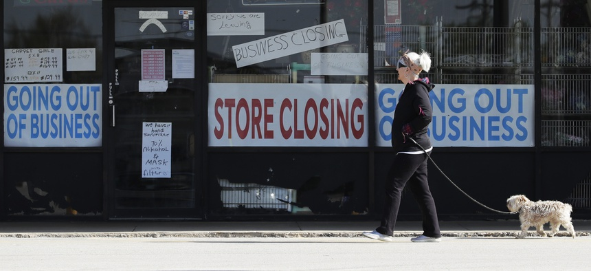 A woman takes walk with a dog in front of the closing signs displayed in a store's window front in Niles, Ill., Wednesday, May 13, 2020.