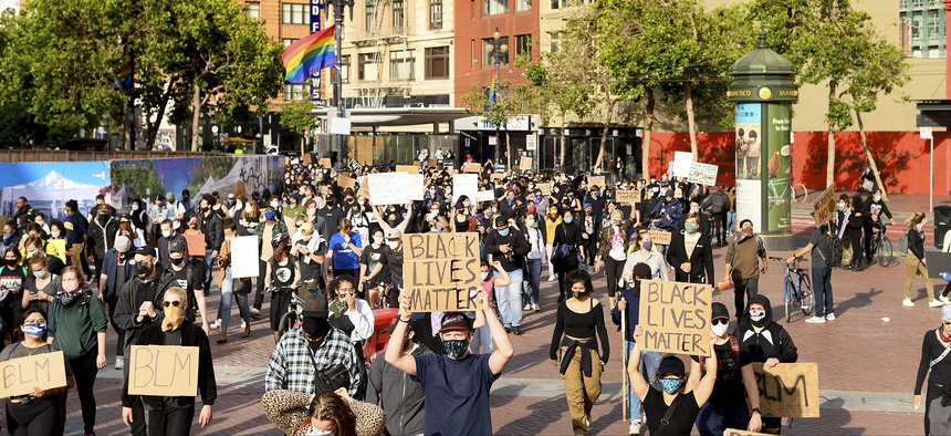 Demonstrators march in San Francisco on Sunday, May 31, 2020, protesting the death of George Floyd, who died after being restrained by Minneapolis police officers on May 25.