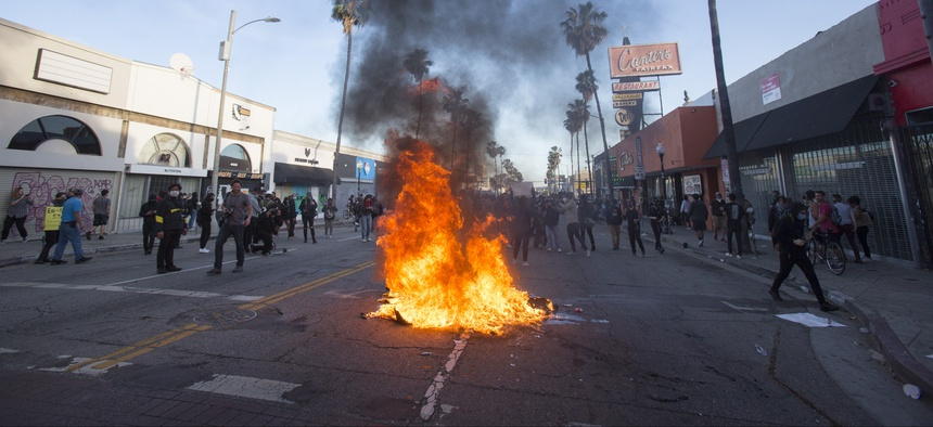 A fire is set on the street during a protest over the death of George Floyd, a handcuffed black man in police custody in Minneapolis, in Los Angeles, Saturday, May 30, 2020.