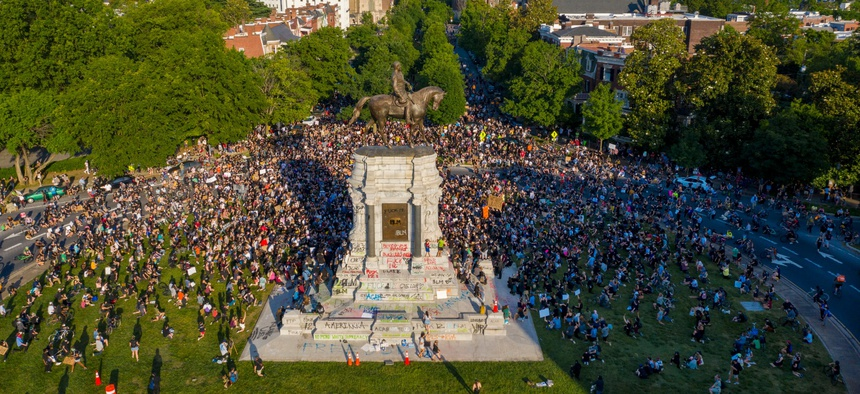 """In this photo taken with a drone, a large group of protesters gather around the statue of Confederate General Robert E. Lee on Monument Avenue near downtown on June 2, 2020, in Richmond, Va. The crowd protesting police brutality chanted """"Tear it down."""""""