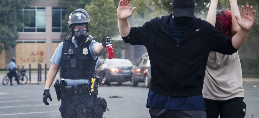 A police officer, Sunday, May 31, 2020, unloads pepper spray at protesters with their hands raised in Minneapolis