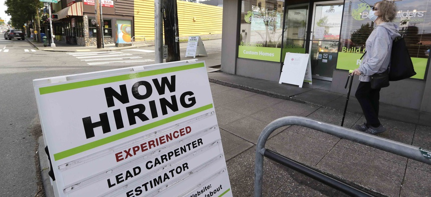 In this photo taken Thursday, June 4, 2020, a pedestrian wearing a mask walks past reader board advertising a job opening for a remodeling company, in Seattle.