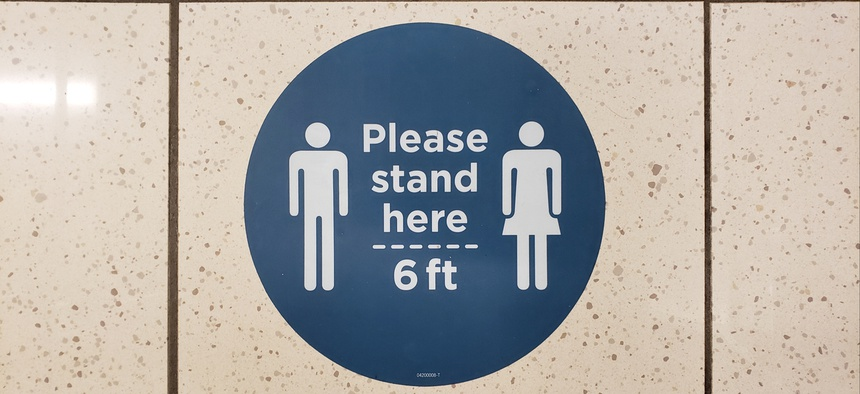 Some reopened businesses have put signs on the floor reminding customers to socially distance.