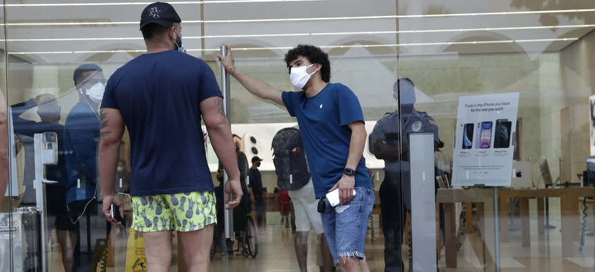 An employee wearing a protective face covering, right, monitors the flow of customers at an Apple retail store along Lincoln Road Mall during the new coronavirus pandemic, Wednesday, June 17, 2020, in Miami Beach, Fla. (AP Photo/Lynne Sladky)