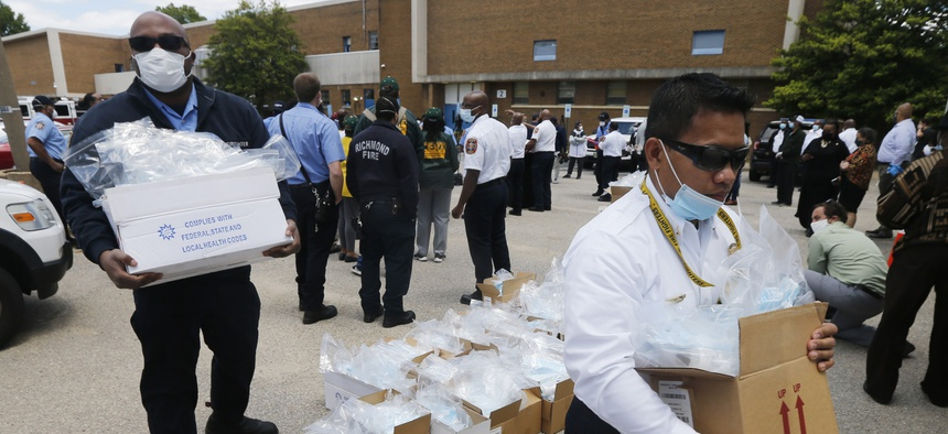 Volunteer firefighters load boxes of personal protective equipment during a health equity community event Tuesday May 12, 2020, in Richmond, Va.