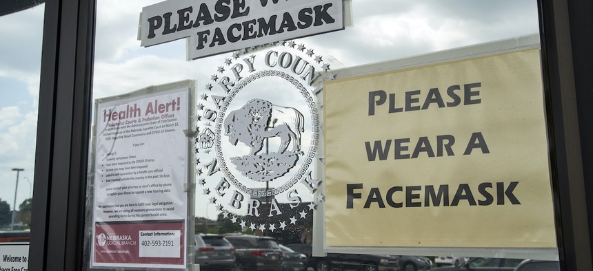 Signs encourage the wearing of face masks Thursday, June 18, 2020, at a Sarpy County office in Papillion, Neb., where face covering is recommended but not mandatory.