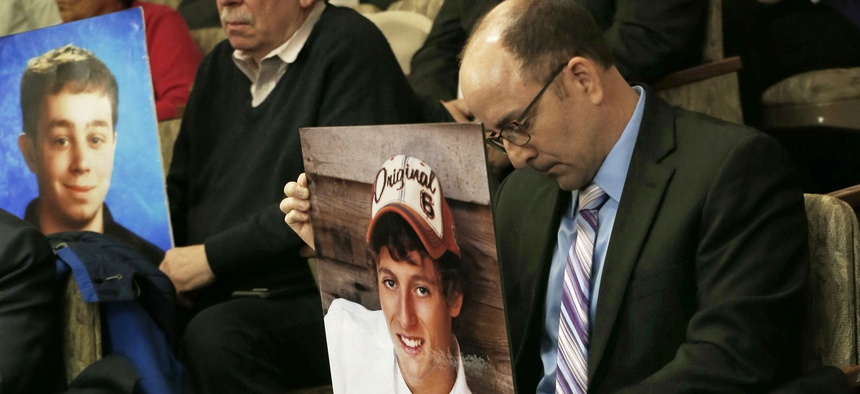 Greg LaVallee, right, testifies at a legislative hearing in Minnesota last year, holding a photo of his son, who was killed by a driver who was using a cellphone.