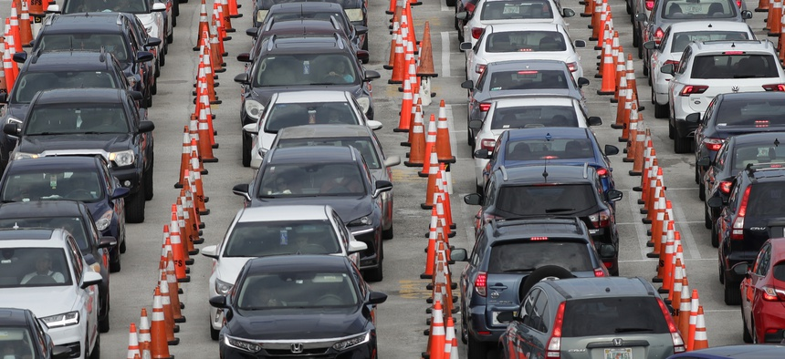 Lines of cars wait at a drive-through coronavirus testing site on July 5, 2020, outside Hard Rock Stadium in Miami Gardens, Fla.