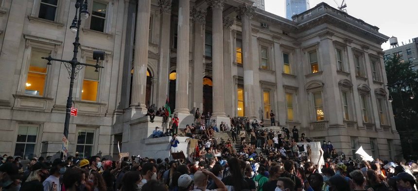 Protestors gather outside City Hall in New York City on June 30, 2020 during lawmakers debate over the police budget.