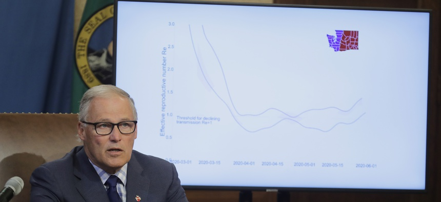 """Washington Gov. Jay Inslee speaks at a news conference showing a chart of the """"reproductive number"""" of each case of the coronavirus in the eastern and western parts of the state. Data and evidence have become instrumental in governors decision-making."""