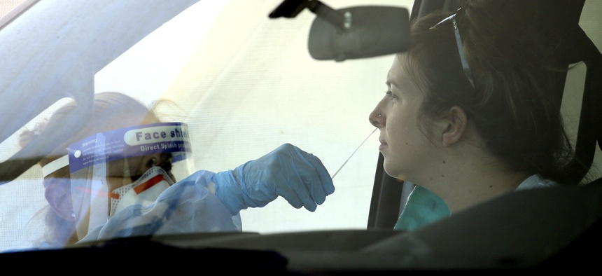 People get tested at a drive thru coronavirus testing site at South Mountain Community College, Thursday, July 9, 2020, in Phoenix.