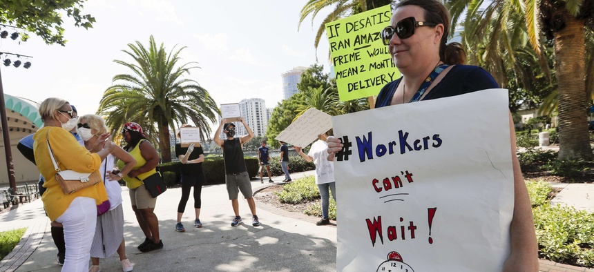 A small group of demonstrators gathers at Lake Eola Park to protest the Florida unemployment benefits system, Wednesday, June 10, 2020, in Orlando, Fla.