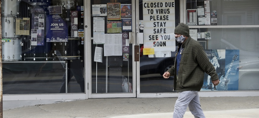 """A man wearing a mask walks past """"The Music Emporium,"""" during the coronavirus pandemic on May 6, 2020, in Cleveland."""