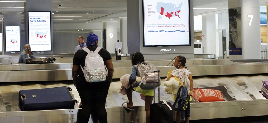 Travelers arriving from Atlanta await their luggage in the baggage claim area of Terminal B at LaGuardia Airport, Thursday, June 25, 2020, in New York.