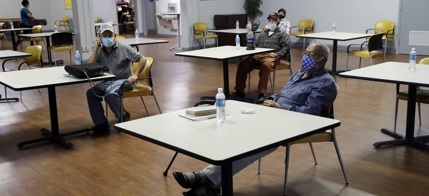 A group of men sit with socialdistincing inside an air conditioned room at a cooling center as temperatures rise amid the COVID-19 pandemic Wednesday, May 6, 2020, in Los Angeles.