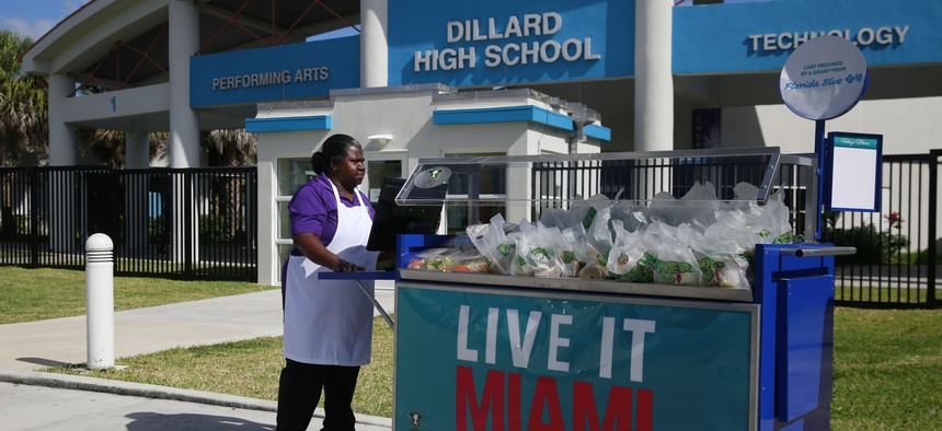 A cafeteria worker pushes a cart full of food to distribute a free lunch to the students and community at Dillard High School amid the coronavirus outbreak and school closings on March 16, 2020, in Fort Lauderdale, Fla.