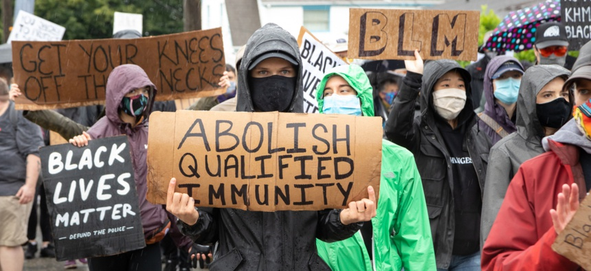 A protester in Washington holds a sign calling for the end of qualified immunity.