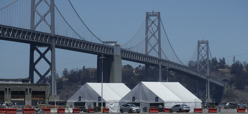 A Covid-19 testing site sits in front of the San Francisco-Oakland Bay Bridge during the coronavirus outbreak in San Francisco, Saturday, July 11, 2020. (AP Photo/Jeff Chiu)