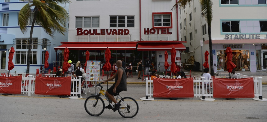 People are seen on Ocean Drive as Miami Dade County is mandating a daily 8 p.m. to 6 a.m. curfew.