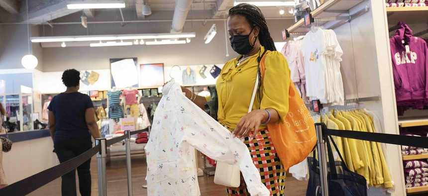 In this June 30, 2020, photo, a woman shops for clothing in a Gap store during the coronavirus pandemic, in New York.