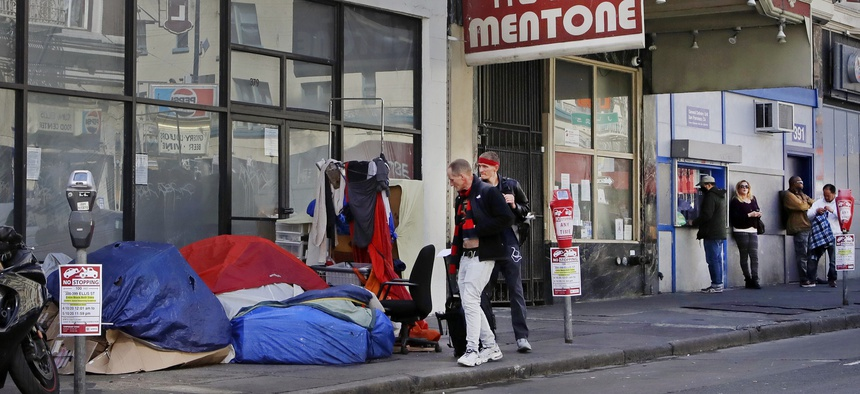 In this Monday, April 13, 2020, file photo, pedestrians walk to the edge of the sidewalk to avoid stepping on people in tents and sleeping bags in the Tenderloin area of San Francisco.