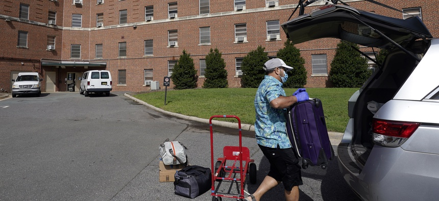 A parent packs a student's belongings at Ehringhaus dormitory following a cluster of COVID-19 cases on campus at the University of North Carolina in Chapel Hill, N.C., Tuesday, Aug. 18, 2020.