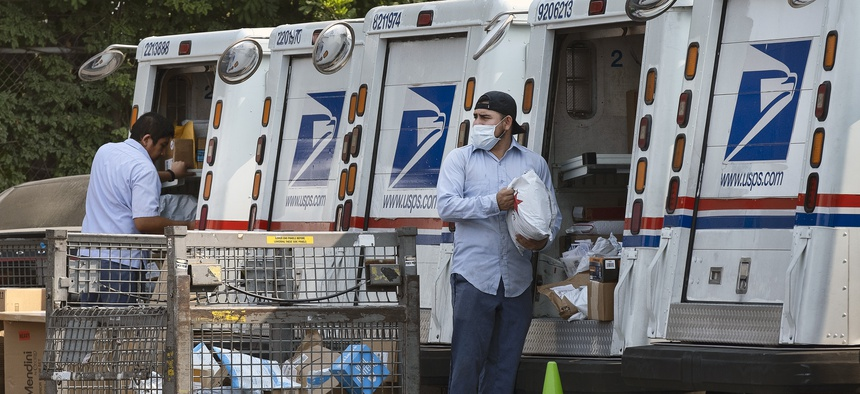 Postal workers load packages in their mail delivery vehicles at the Panorama city post office on Aug. 20, 2020 in the Panorama City section of Los Angeles.