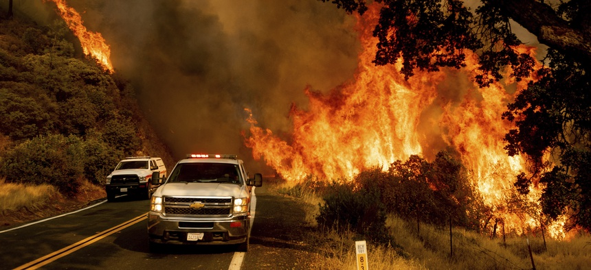 Flames from the LNU Lightning Complex fires jump Butts Canyon Rd. on Aug. 23, 2020, as firefighters work to contain the blaze in unincorporated Lake County.