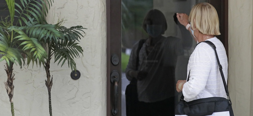 A census taker knocks on the door of a residence on Aug. 11, 2020, in Winter Park, Fla.