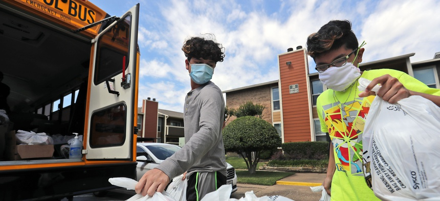Amid concerns of the spread of COVID-19, brothers Brian, left, and David Rayo wear masks as they pick up school lunches for themselves and other siblings at their apartment complex in Dallas, Tuesday, May 5, 2020.