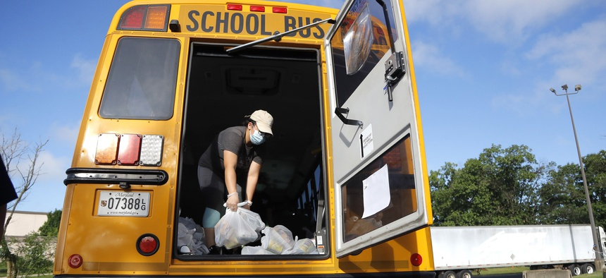 A bus driver with the Montgomery County School District helps load a bus with bags of food to be donated to residents, Friday, July 10, 2020, in Derwood, Md.
