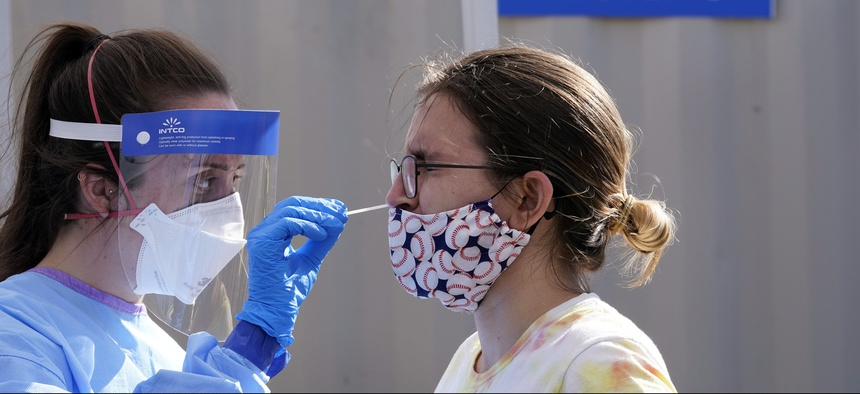 A woman is tested for Covid-19 at a walk-up testing site in Seattle. Auditors from nearly a dozen states are planning to review how pandemic data is being tracked.