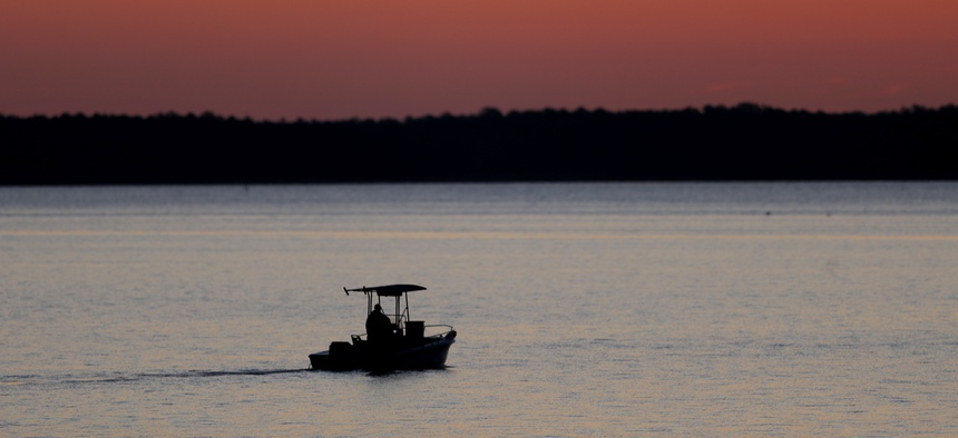 In this May 14, 2020 photo, a small boat chugs along the Honga River near the Chesapeake Bay as the sky lights up at sunrise, in Fishing Creek, Md.