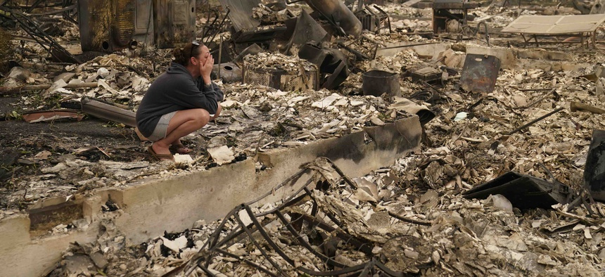 A woman cries as she visits her home destroyed by the Almeda Fire, Friday, Sept. 11, 2020, in Talent, Ore.