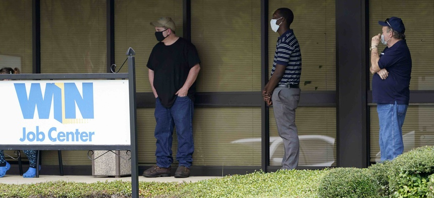 In this Aug. 31, 2020 photo, clients line up outside the Mississippi Department of Employment Security WIN Job Center in Pearl, Miss.