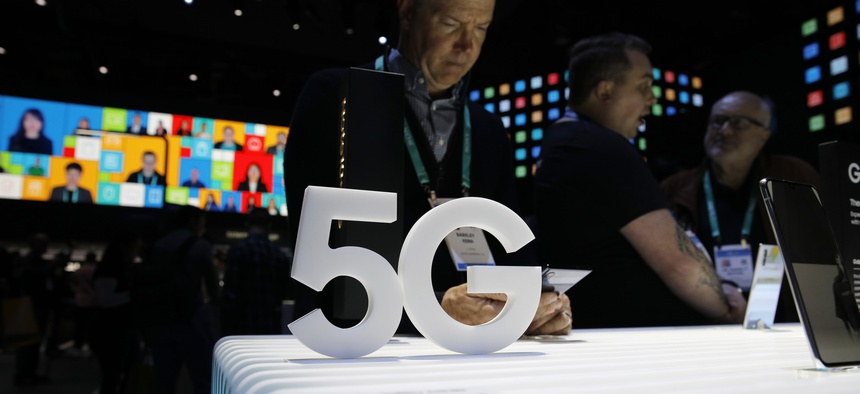 People loook at 5G phones at the Samsung booth during the CES tech show, Tuesday, Jan. 7, 2020, in Las Vegas.