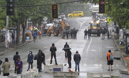 Protesters stand on barricades a block away as Seattle Department of Transportation workers remove other barricades Tuesday, June 30, 2020 at the CHOP (Capitol Hill Occupied Protest) zone in Seattle.