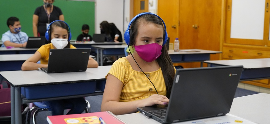 Reyna Najera, front, and her sister, Brenda, work on a laptops in a classroom in Newlon Elementary School on Aug. 25, 2020, which is one of 55 Discovery Link sites set up by Denver Public Schools for students to do remote learning.