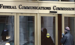In this Thursday, Dec. 14, 2017, file photo, a person with a smartphone enters the Federal Communications Commission building in Washington.