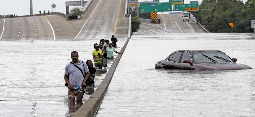 In this Aug. 27, 2017 file photo, evacuees wade down a flooded section of Interstate 610 as floodwaters from Tropical Storm Harvey in Houston.