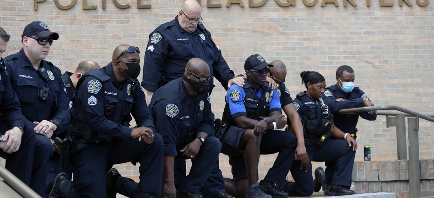 Members of the Austin Police Department kneel in front of demonstrators who gathered in Austin, Texas on June 6, 2020, to protest the death of George Floyd, a black man who was in police custody in Minneapolis.