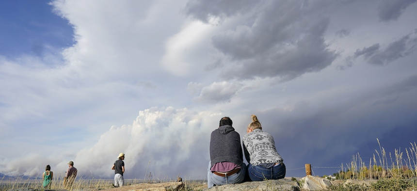 A couple sit on rocks at the overlook along Highway 36 to watch a smoke plume grow as several wildfires burn in northern and western Colorado and smoke funnels on to the eastern plains Saturday, Oct. 17, 2020, near Boulder, Colo.